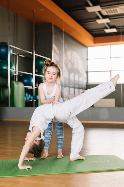 Criança menina sorridente, ajudando, dela, irmã, para, exercitar, em, ginásio Foto gratuita