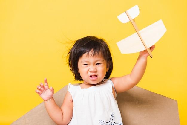 Criança menina sorriso usar chapéu piloto brincar com asas de avião de papelão de brinquedo Foto Premium
