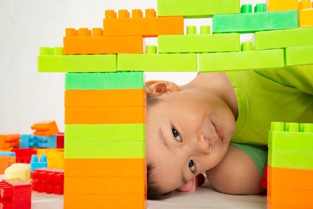 Criança menino jogando tijolo plástico bloco colorido com feliz Foto Premium