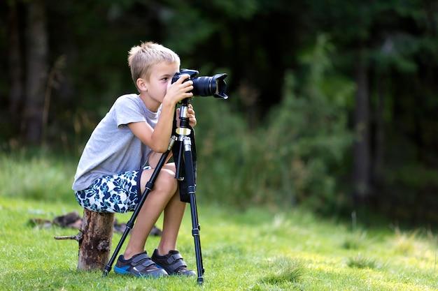 Criança menino tirando foto com a câmera de tripé. Foto Premium