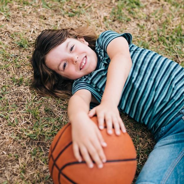 Criança, mentir grama, e, segurando bola Foto gratuita