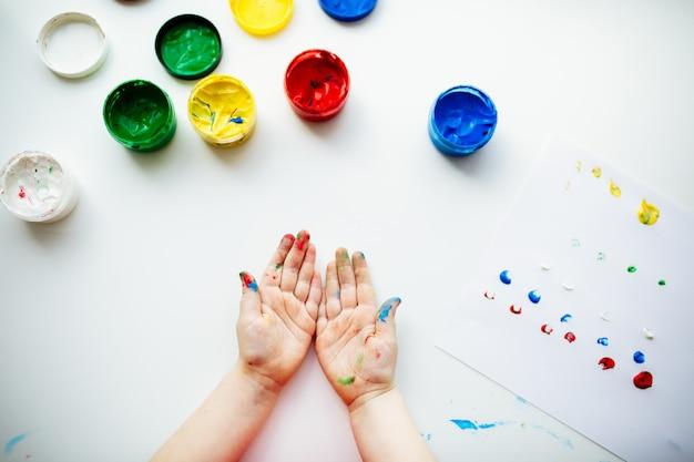 Criança mostra suas mãos manchadas com tinta na mesa com materiais de arte, vista superior Foto Premium