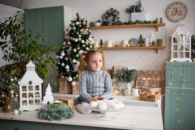 Criança na cozinha de manhã de natal em casa. Foto Premium
