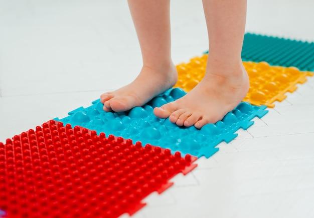 Criança na esteira de massagem nos pés do bebê. exercícios para as pernas no tapete de massagem ortopédica. Foto Premium