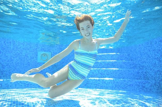 Criança nada debaixo d'água na piscina, garota adolescente ativo feliz mergulha e se diverte sob a água, fitness criança e esporte em férias em família no resort Foto Premium