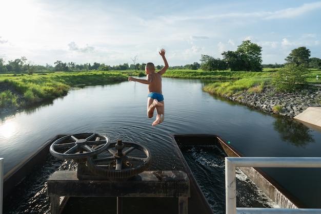 Criança no ar ao saltar no lago com bela sunray - cenário de natureza de verão Foto Premium