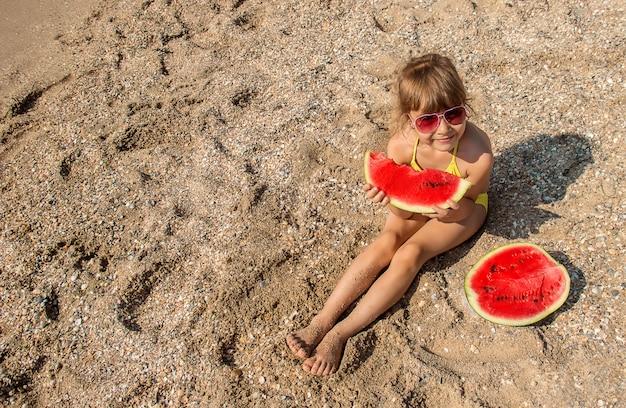 Criança no mar comendo uma melancia. Foto Premium