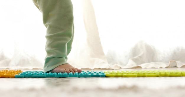 Criança no tapete de massagem fazendo exercícios para prevenção de pés chatos Foto Premium