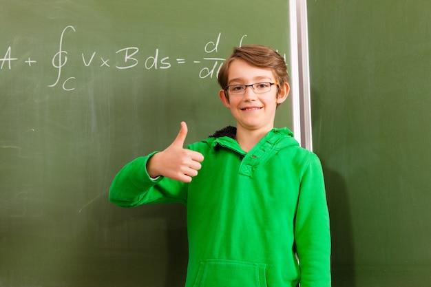 Criança ou aluno no quadro-negro na escola Foto Premium