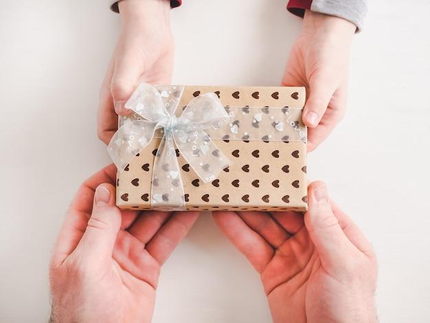 Criança parabeniza seu pai. caixa de presente bonita Foto Premium