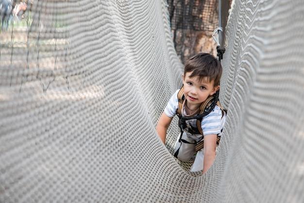 Criança pequena ativa que joga na rede de escalada. crianças brincam e escalam ao ar livre num dia ensolarado de verão. Foto Premium