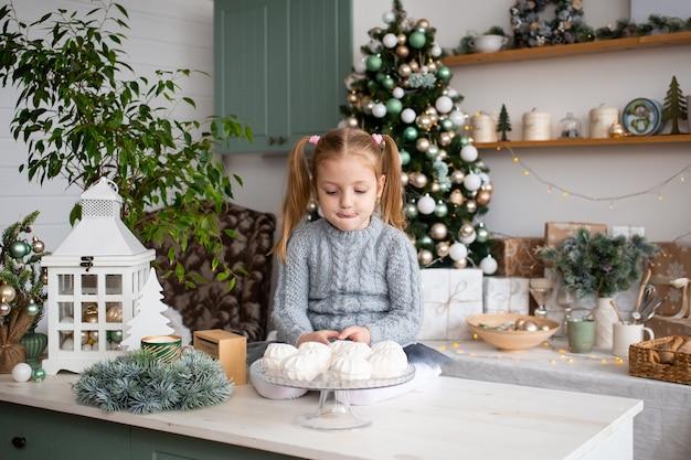 Criança pequena bonita na cozinha em casa de natal. Foto Premium