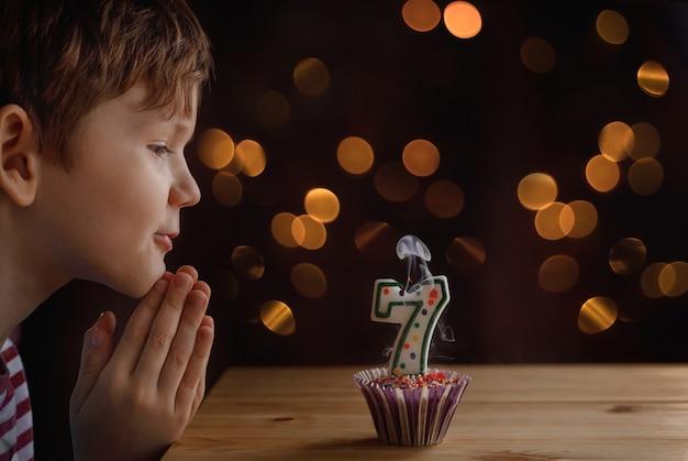 Criança pequena bonito que funde velas em bolos de aniversário. Foto Premium