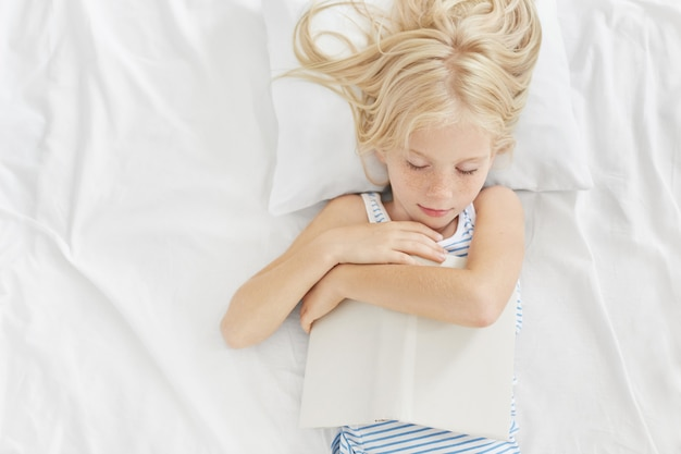 Criança pequena com aparência bonita dormindo depois de ler histórias interessantes na cama, mantendo o livro nas mãos, deitado no travesseiro branco e roupas de cama, tendo sonhos agradáveis. lendo antes de dormir Foto gratuita