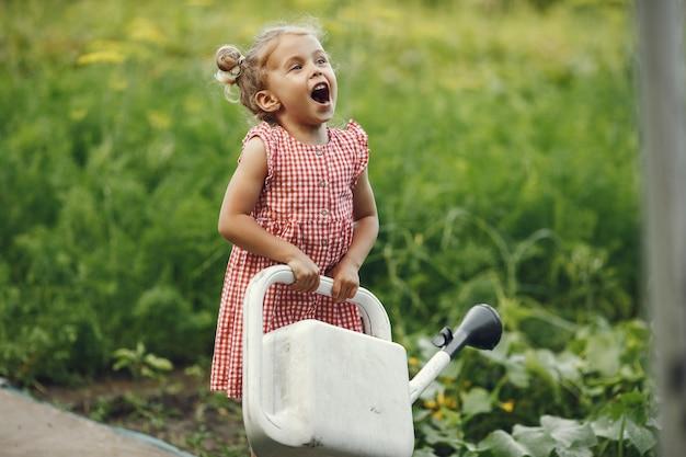 Criança pequena com um regador com flores despeje. menina com um funil. criança em um vestido rosa. Foto gratuita