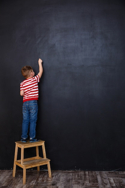 Criança pequena em pé em uma cadeira e desenho Foto gratuita