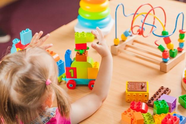 Criança pequena sentada e brincando Foto Premium