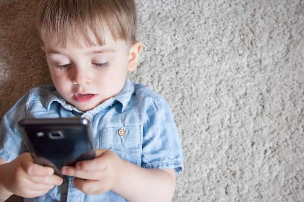 Criança pequena viciada em jogar jogos com o telefone. controle parental para dispositivos eletrônicos em crianças. Foto Premium