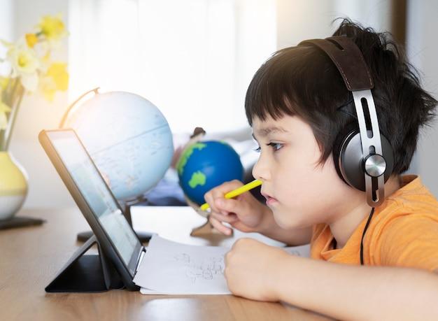 Criança pré-escolar usando tablet e usando fones de ouvido Foto Premium