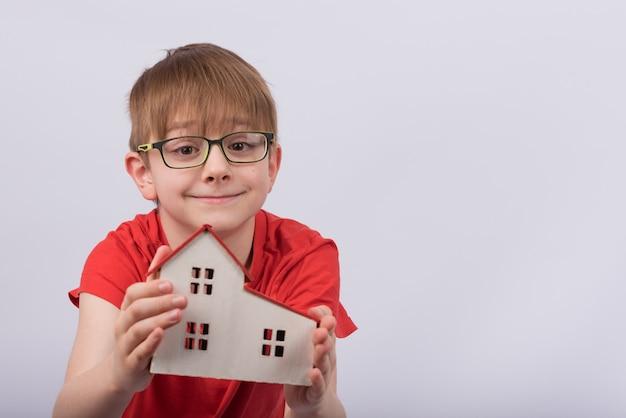 Criança que guarda o modelo da casa no espaço em branco. garoto bonito de óculos, segurando a casa de brinquedo. educação escolar em casa Foto Premium