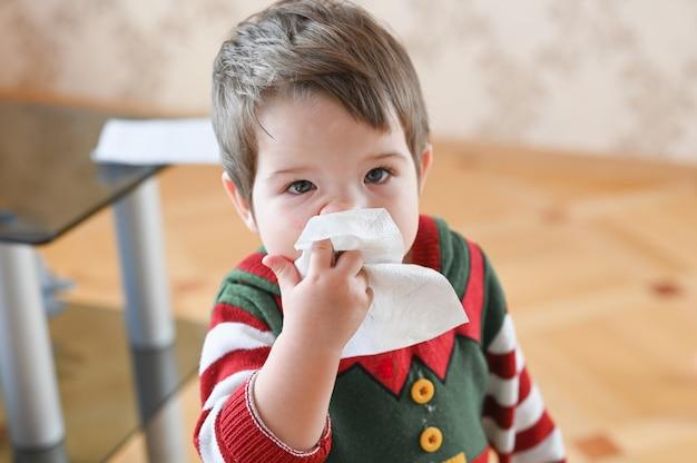 Criança que sofre de corrimento nasal ou espirros. garotinho alérgico Foto Premium