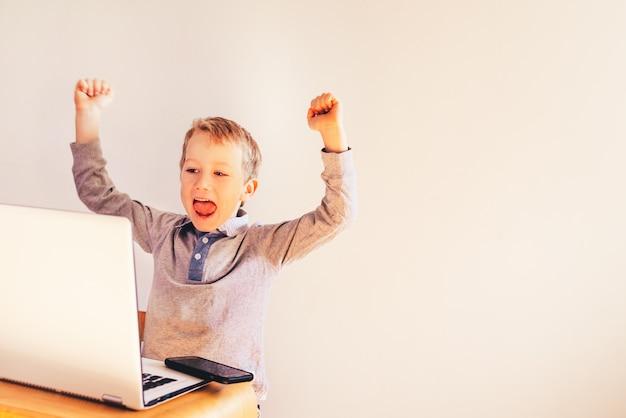 Criança que usa um portátil e rindo de seu sucesso no negócio. Foto Premium