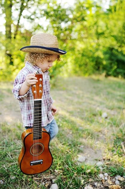 Criança ruiva cacheada em um chapéu de palha Foto Premium