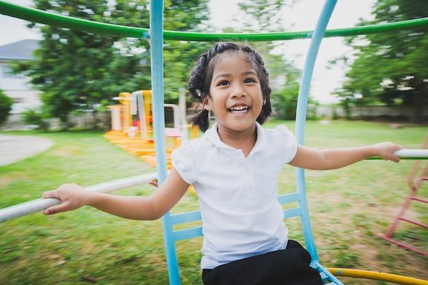 Criança saudável está brincando no quintal, feliz com os balanços, cavalos de balanço, carruagens de slides. Foto Premium