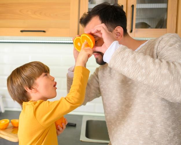 Criança segurando metades de laranjas para seu pai Foto gratuita