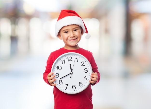 Criança segurando um relógio na frente de seu peito Foto gratuita