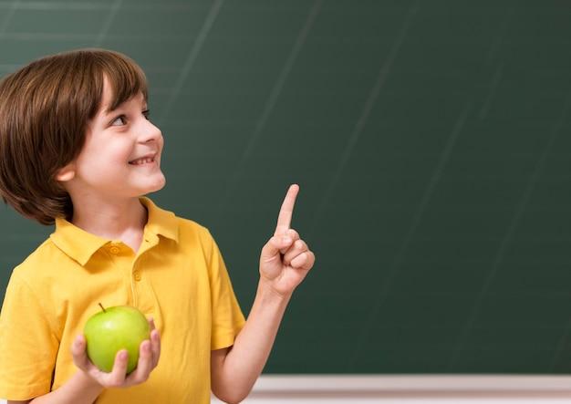Criança segurando uma maçã enquanto aponta para cima Foto gratuita