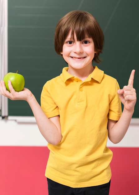 Criança segurando uma maçã verde Foto gratuita