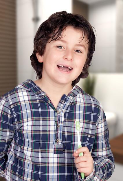 Criança sem alguns dentes escovando os dentes no banheiro Foto Premium