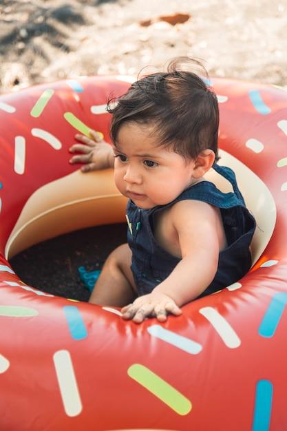 Criança sentada na areia no círculo de natação Foto gratuita