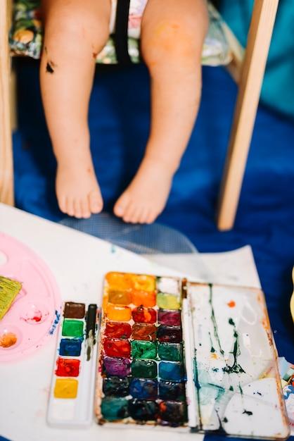Criança sentada perto de cores de água e papel Foto gratuita