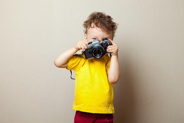 Criança sorridente alegre segurando uma câmera instantânea Foto Premium