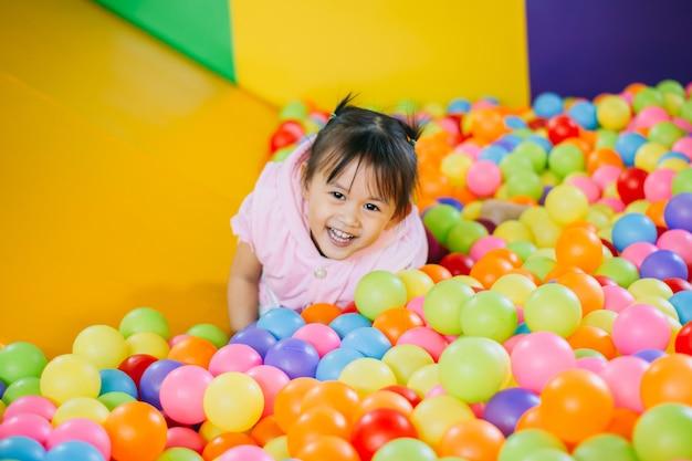 Criança sorridente brincando na piscina de bolas coloridas. Foto Premium