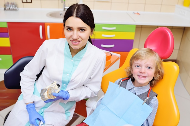 Criança sorridente com cabelo encaracolado luz no exame na cadeira odontológica Foto Premium