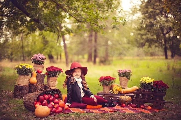 Criança sorridente com cesta de maçãs vermelhas, sentado no parque outono Foto Premium