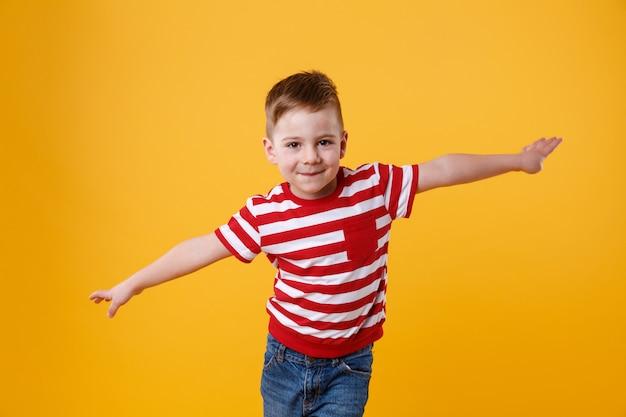 Criança sorridente em pé com as mãos espalhadas Foto gratuita