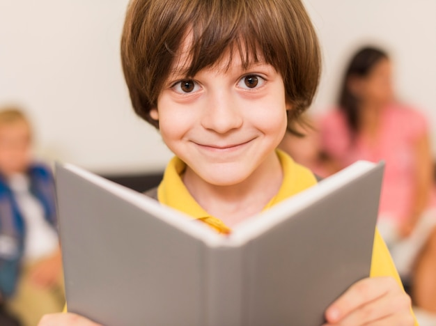 Criança sorrindo enquanto segura um livro Foto gratuita