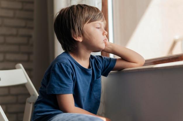 Criança triste olhando pela janela durante a quarentena Foto gratuita