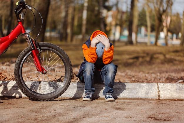 Criança triste sentada perto de uma bicicleta quebrada Foto Premium