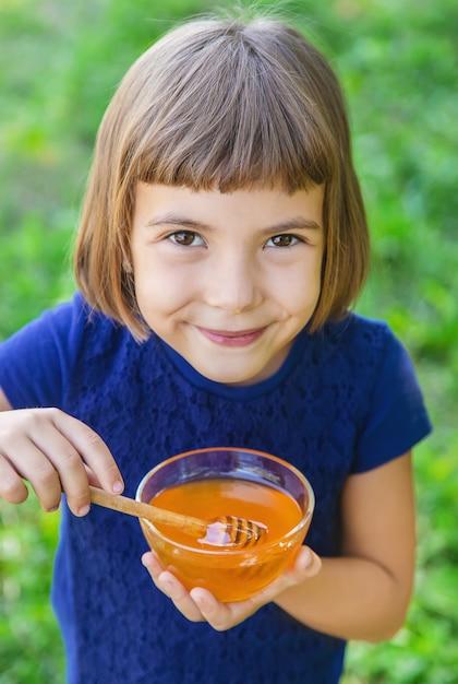Criança um prato de mel nas mãos Foto Premium