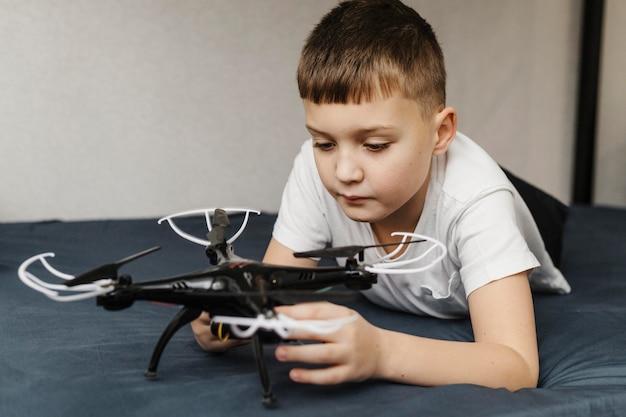 Criança usando drone e ficando na cama Foto Premium