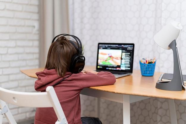 Criança usando fones de ouvido, participando de cursos online Foto gratuita