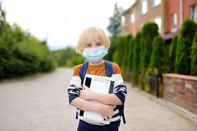 Criança usando máscara facial indo para reabrir a escola Foto Premium
