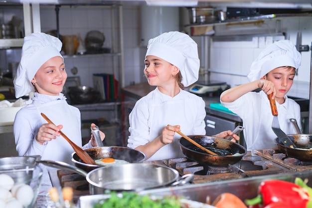 Crianças a cozinhar o almoço na cozinha de um restaurante. Foto Premium