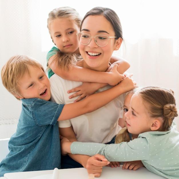 Crianças abraçando seu professor Foto gratuita