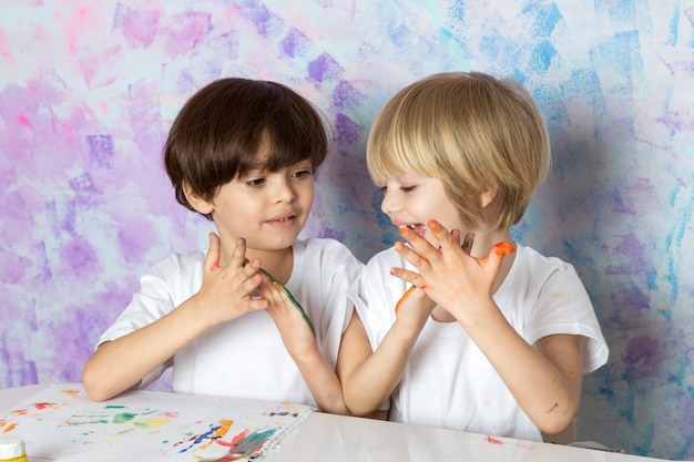 Crianças adoráveis em camisetas brancas, brincando com tintas multicoloridas Foto gratuita